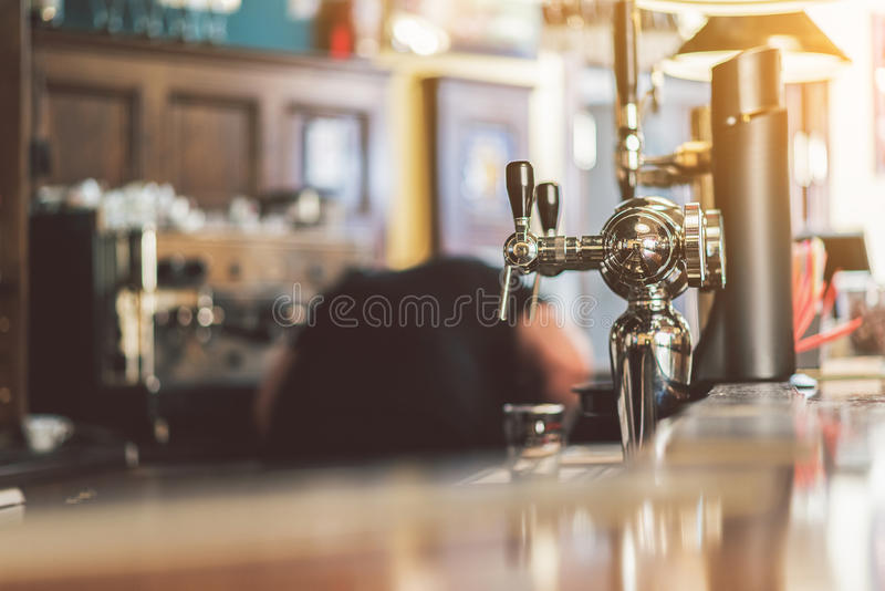 Working atmosphere in popular pub. Bar counter. Close-up of modern beer taps in pub. Barman laboring in the background stock photos