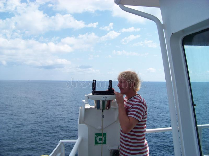 Working with azimuth device on merchant ship near coast stock photo