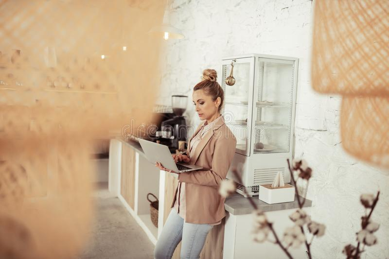 Concentrated woman working at her laptop near coffee table. royalty free stock photos