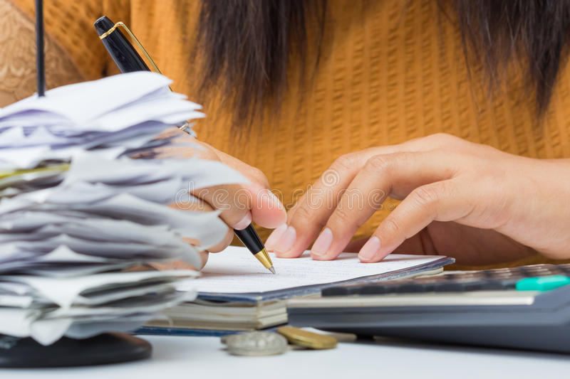Working with bills. Closeup woman's hand writing messages on business desk stock photography