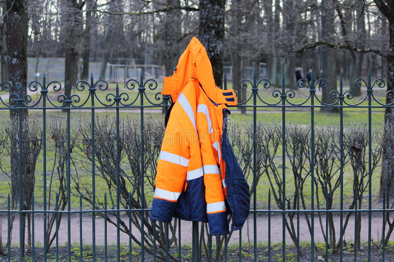 Working blue-orange warm jacket hanging on the fence. Working blue-orange warm jacket hanging on the fence royalty free stock images