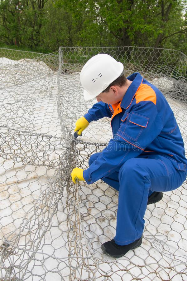 Working in a blue uniform and a white helmet, knit mesh for cells under the stones to improve the shore stock photography
