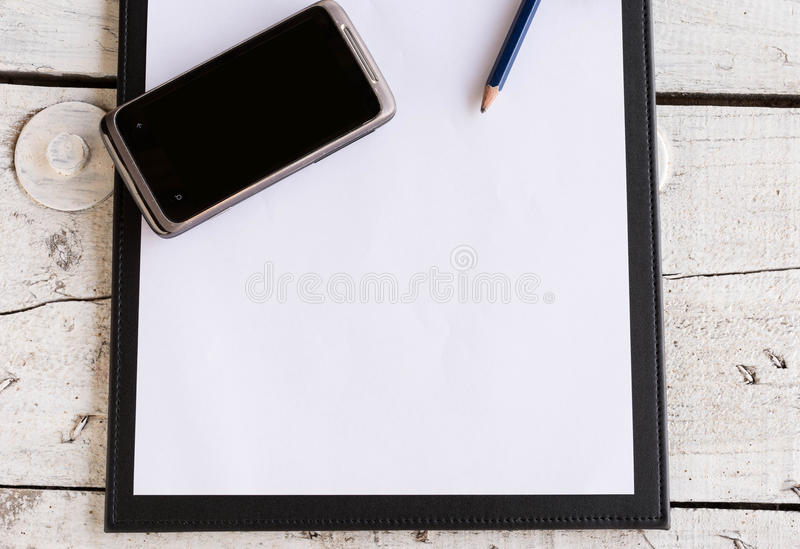 Working board text frame. For your text with moblie phone on wooden table royalty free stock photos