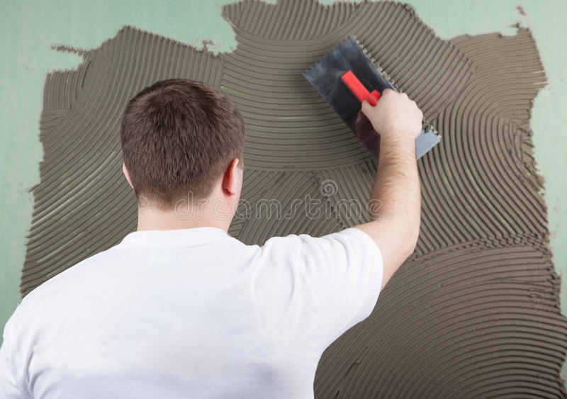 Working builder applies glue on a wall for a ceramic tile. f royalty free stock photography