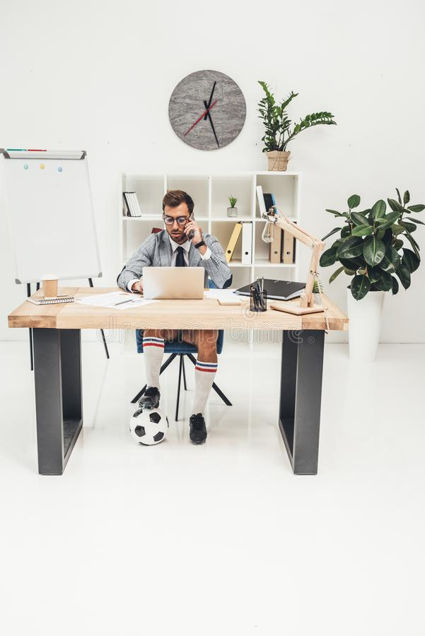 Working businessman in soccer shoes with ball under desk. At workplace royalty free stock photography