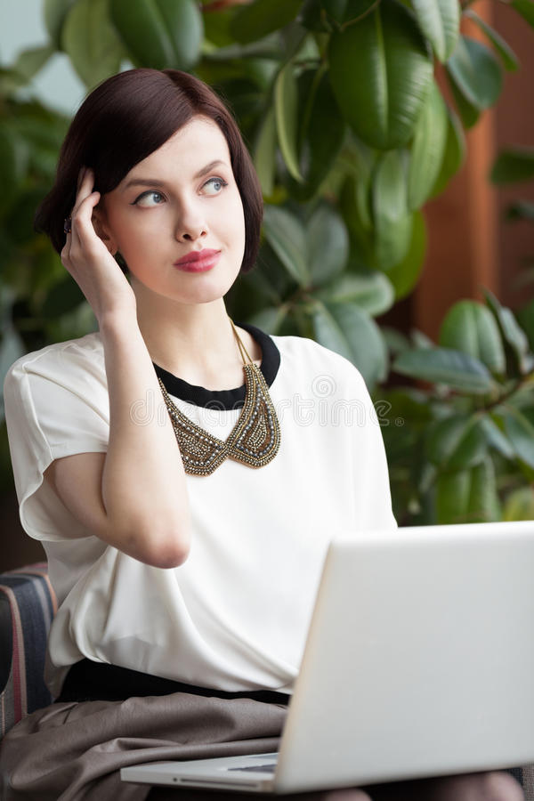 Working in cafe. Attractive woman sitting in cafe with laptop stock images