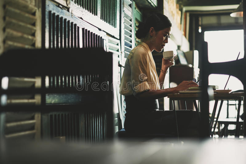 Working at cafe. Pretty business lady drinking coffee and working on laptop in dark cafe stock images