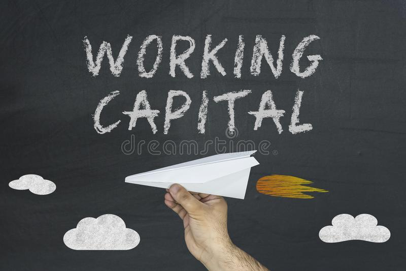 Working Capital concept with flying paper plane on blackboard royalty free stock image