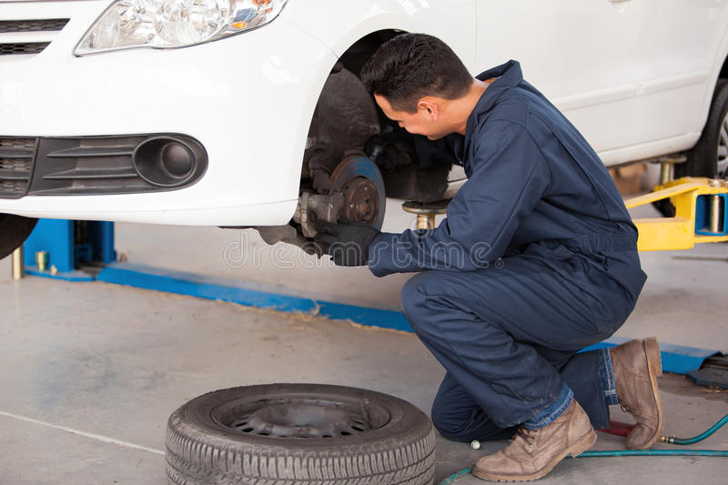 Working on a car brakes. Young mechanic fixing the brakes of a car at an auto shop stock photography