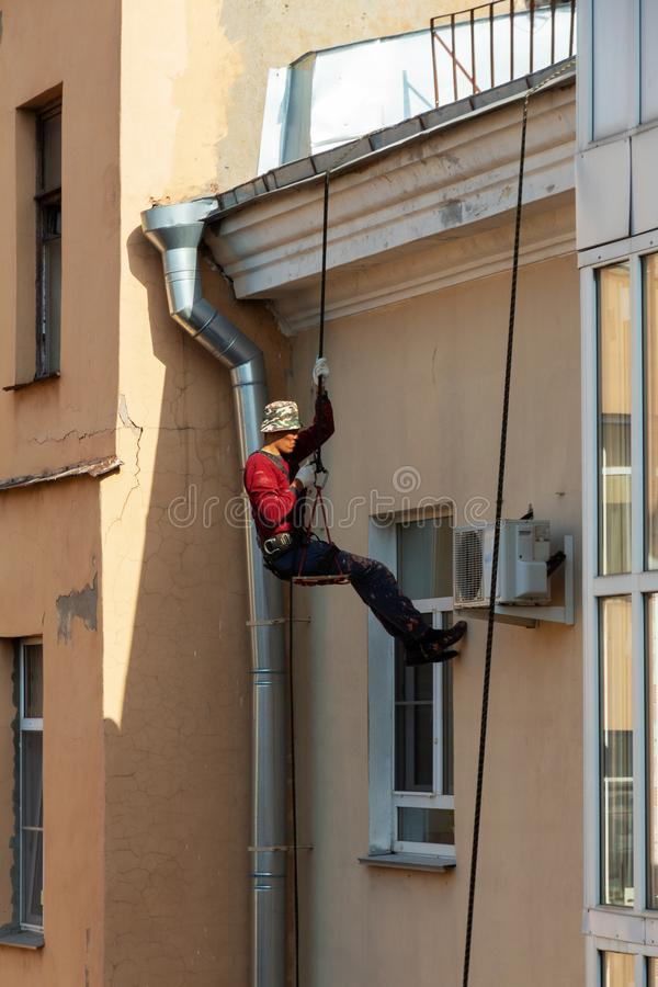Working climber on the rope restores the facade of the house. air conditioner installation and repair stock image