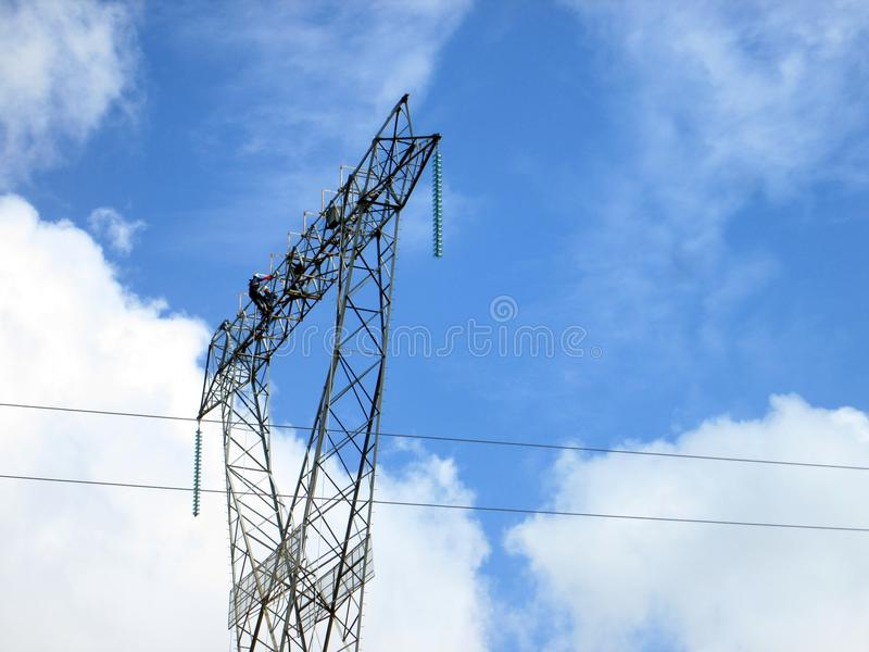 Working between clouds. Several workers installing cables or conductors of electricity and also running maintenance on high voltage tower stock photo