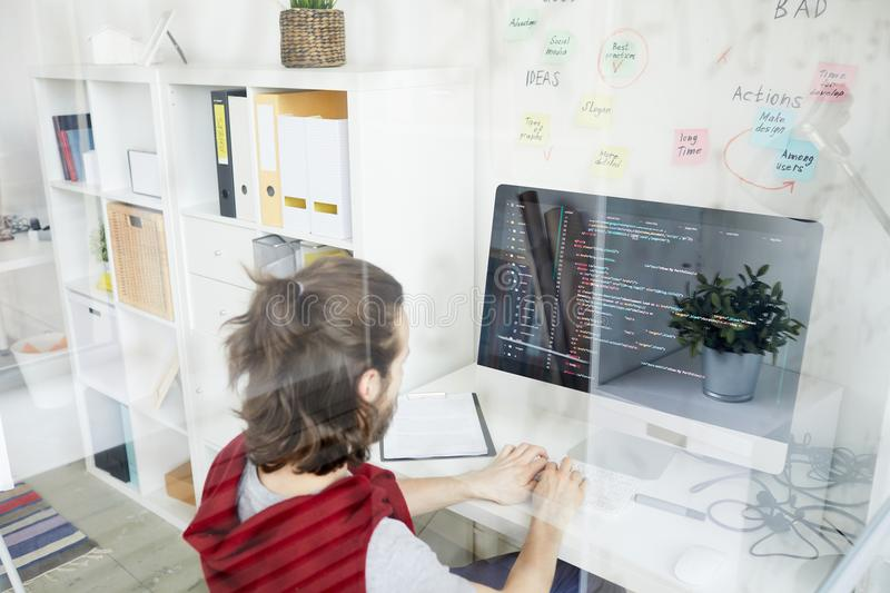Working with coded data. Young it-manager sitting in front of monitor, typing and looking at coded data on screen royalty free stock photos