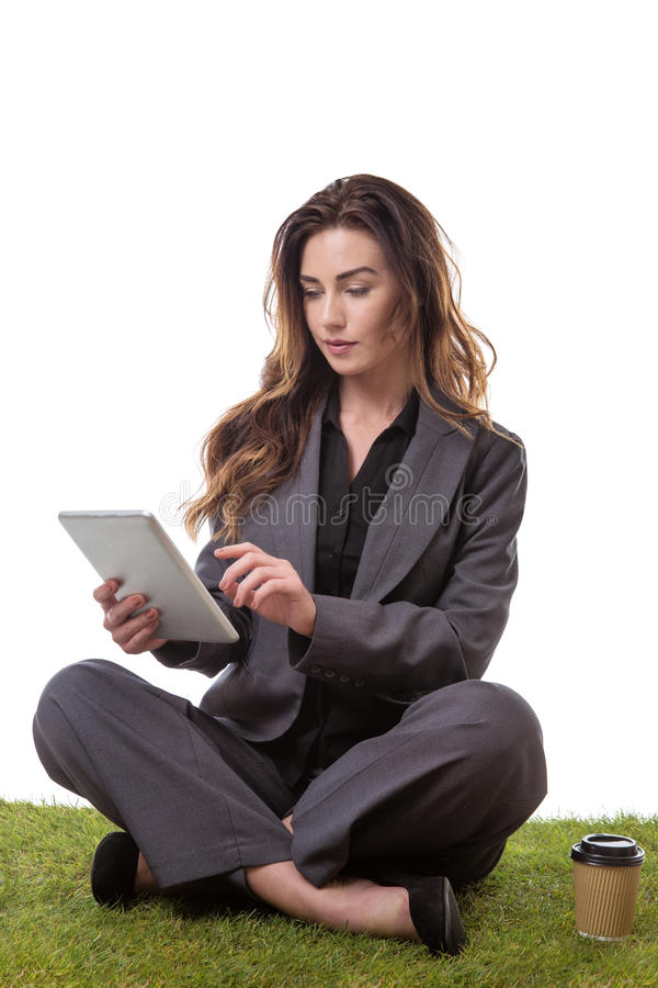Working coffee break. Pretty model, sitting on the grass with crossed legs, on a tablet computer with a takeaway drink royalty free stock photography