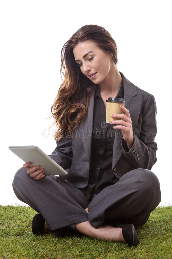 Working coffee break. Pretty model, sitting on the grass with crossed legs, on a tablet computer with a takeaway drink royalty free stock photo