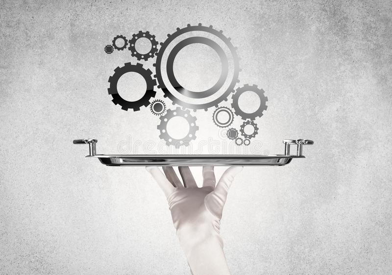 Working cog wheel concept on tray. Crank wheel machine working concept with racks served on silver plate by hand in white glove and industrial grey wall pattern stock photos