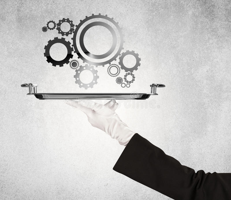 Working cog wheel concept on tray. Crank wheel machine working concept with racks served on silver plate by hand in white glove and industrial grey wall pattern stock photography