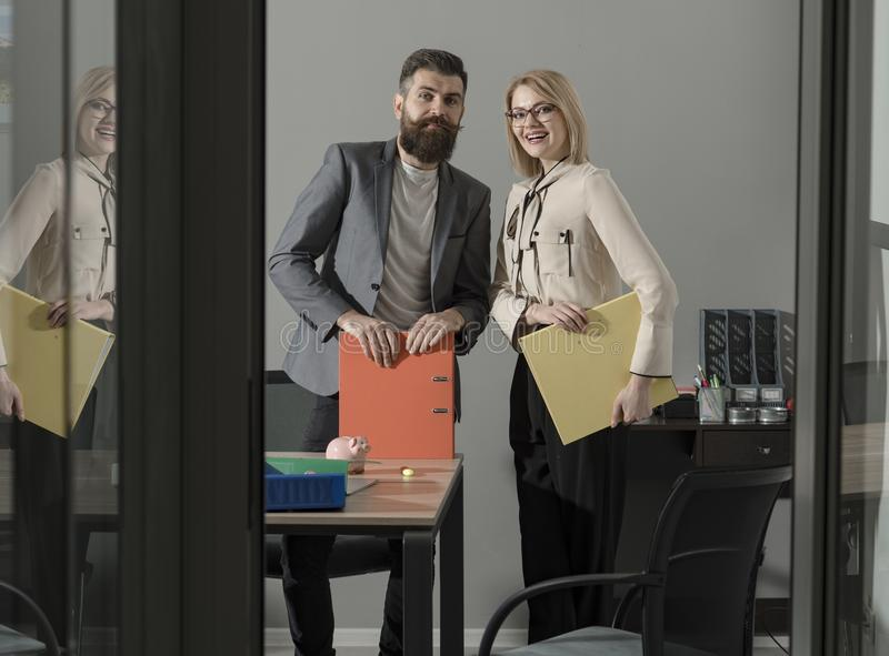 Working and communicating together. Happy colleagues in modern office. Business couple smile meeting in office. Bearded royalty free stock image