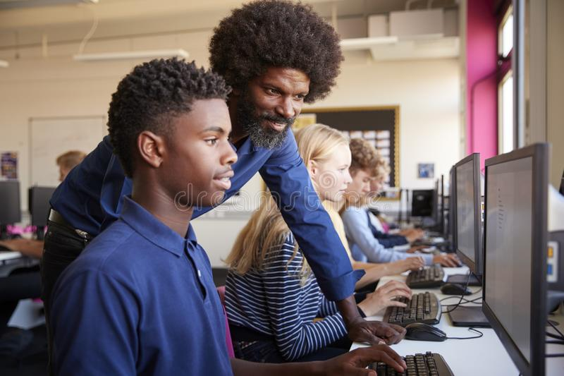 Working In Computer för student för lärareHelping Teenage Male högstadium grupp arkivfoto