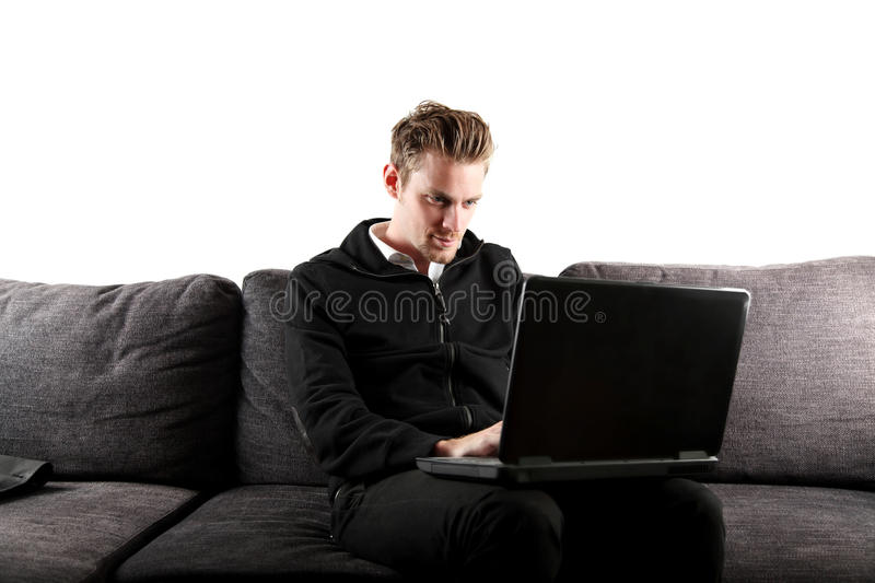 Working on the computer laidback. Young and attractive man wearing a black hoodie and jeans, with a laptop computer in his lap. Sitting down in a sofa. White royalty free stock photography