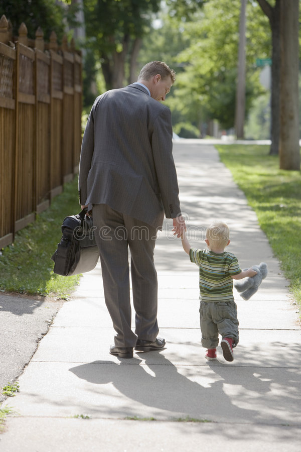 Working Dad walking with son. Professional man walking his child to school or daycare stock image