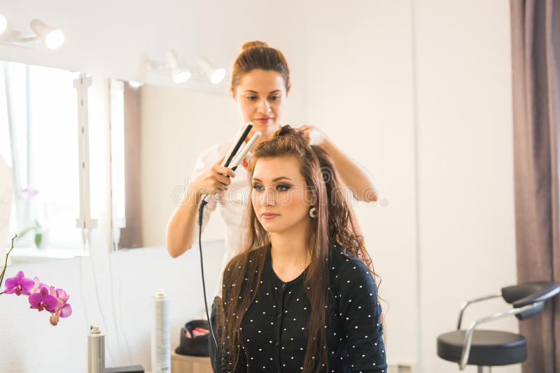 Working day inside the beauty salon. Hairdresser makes hair styling.  royalty free stock images