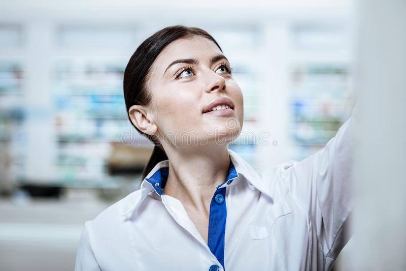 Pretty beaming young woman in a white coat working in a drugstore royalty free stock photo