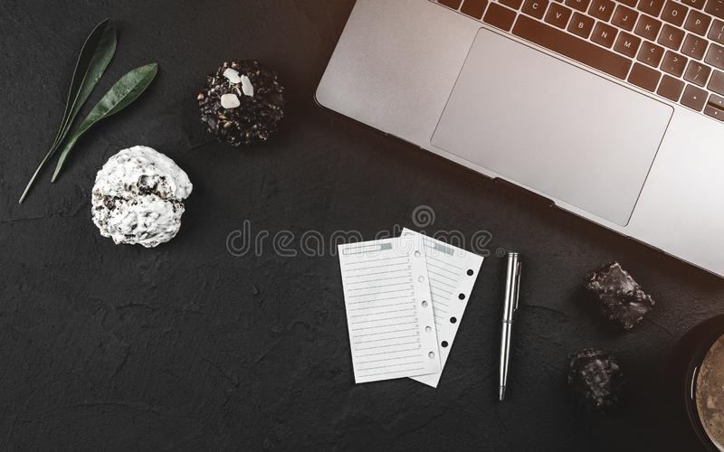 Working desk of a businessman, laptop and some sheets of the agenda, sweets and coffee for break stock photography