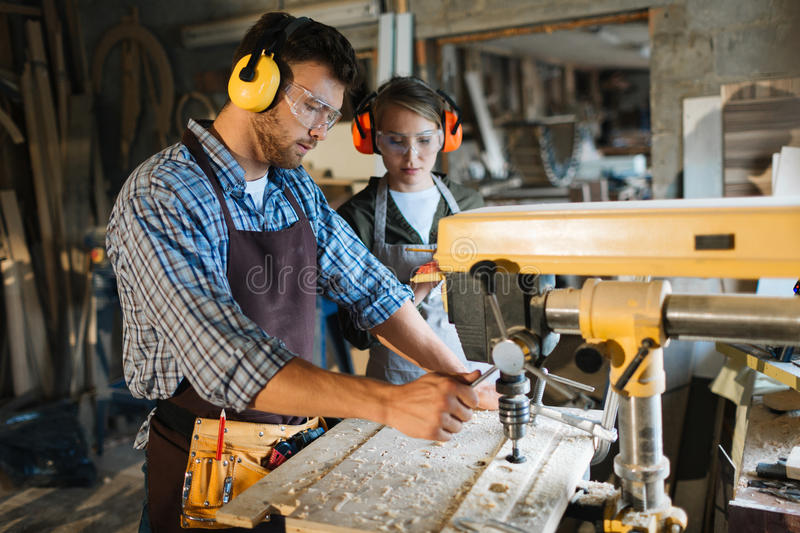 Working by drill machine. Carpenter in uniform and protective headphones working by drill machine royalty free stock images