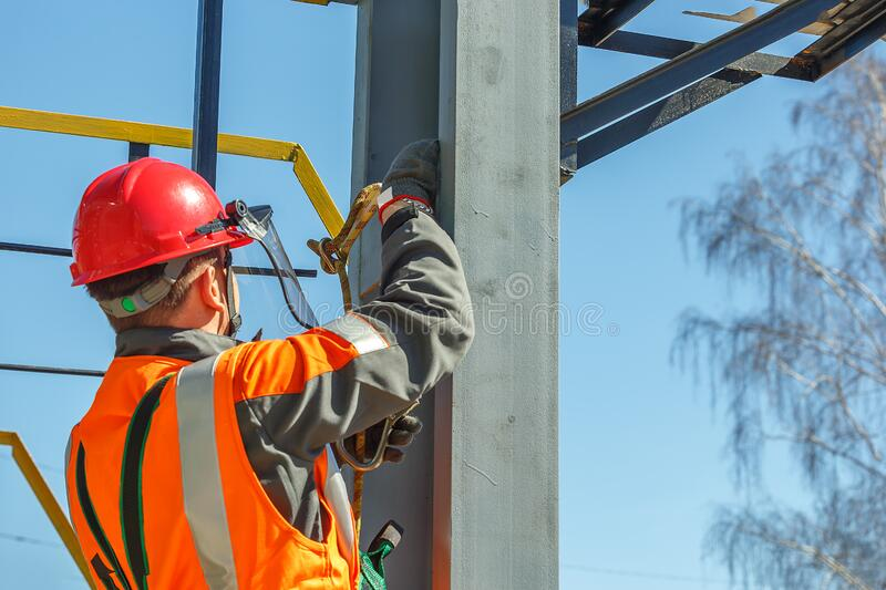 Working electrician hooks a safety rope stock photo