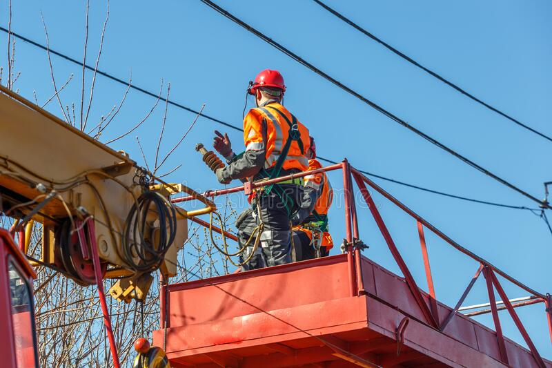 Working electrician looks at the power lines stock images