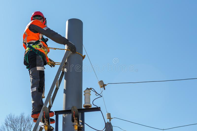 Working electrician tied to the pole with a safety rope royalty free stock image