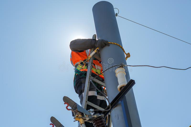 Working electrician tied to the pole with a safety rope royalty free stock photos