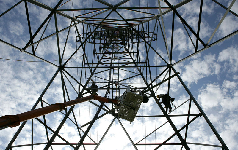 Working in a electricity mast stock photo
