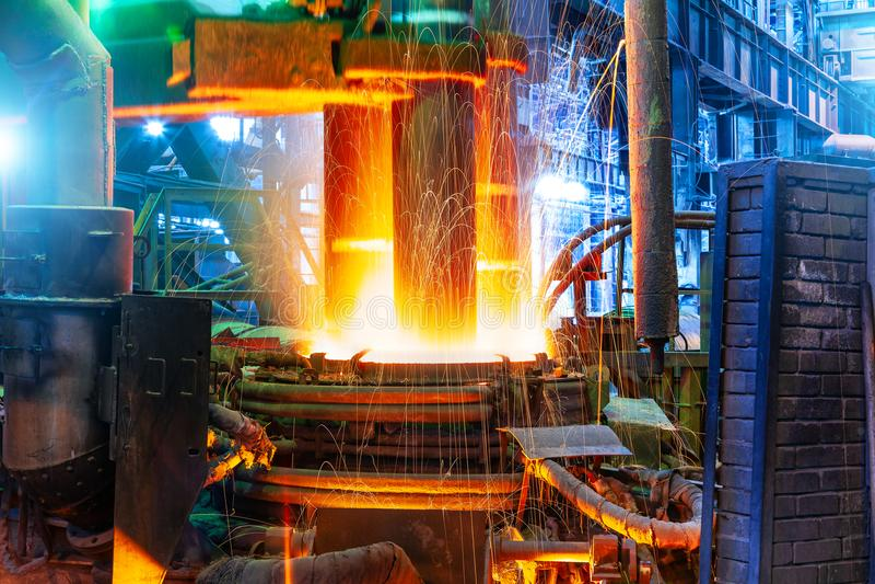 Electroarc furnace at metallurgical plant. Working electroarc furnace at the metallurgical plant workshop stock photo