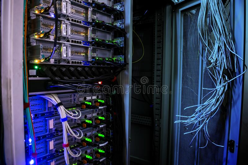Working and empty racks with server equipment are in the data center. Many connected and disconnected cables are in the computer.  stock photos