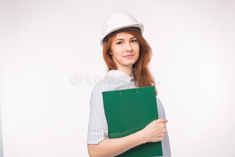 Working, engineering, people concept - a female engineer in a helmet with file over the white background royalty free stock images