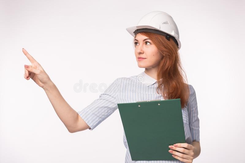 Working, engineering, people concept - Young beautiful redhead girl in architect helmet stock image
