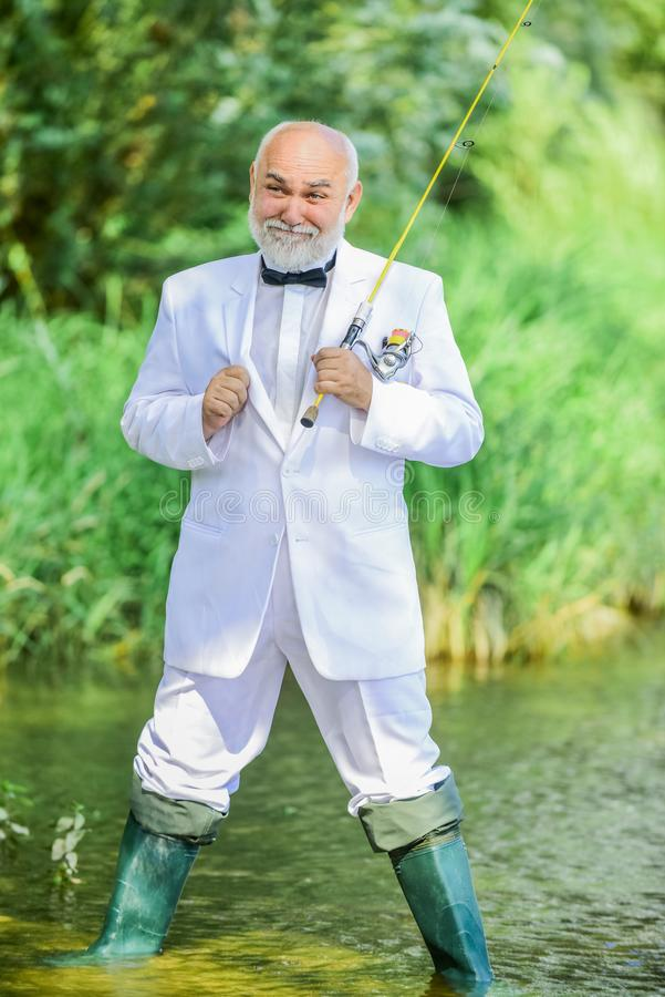 Working everywhere. Fishermen in formal suit. successful catch. business success. mature man fishing. fisher celebrate royalty free stock photo