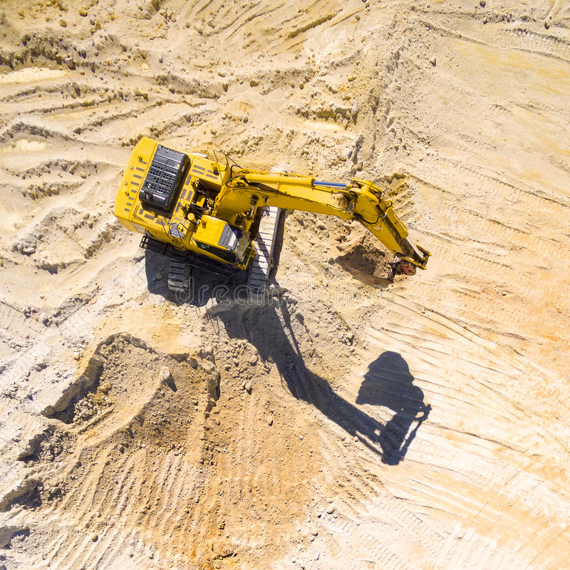 Working excavator in the mine. Aerial view of a working excavator in the mine. Industrial background on mining theme stock image