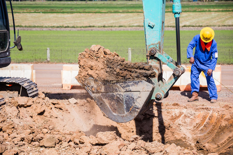 Working Excavator Tractor Digging A Trench. Excavator Tractor Digging A Trench on site royalty free stock photos