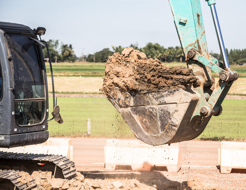 Working Excavator Tractor Digging A Trench. Excavator Tractor Digging A Trench on site royalty free stock image