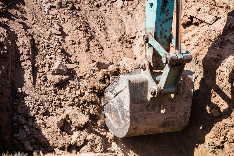 Working Excavator Tractor Digging A Trench. Excavator Tractor Digging A Trench on site royalty free stock images