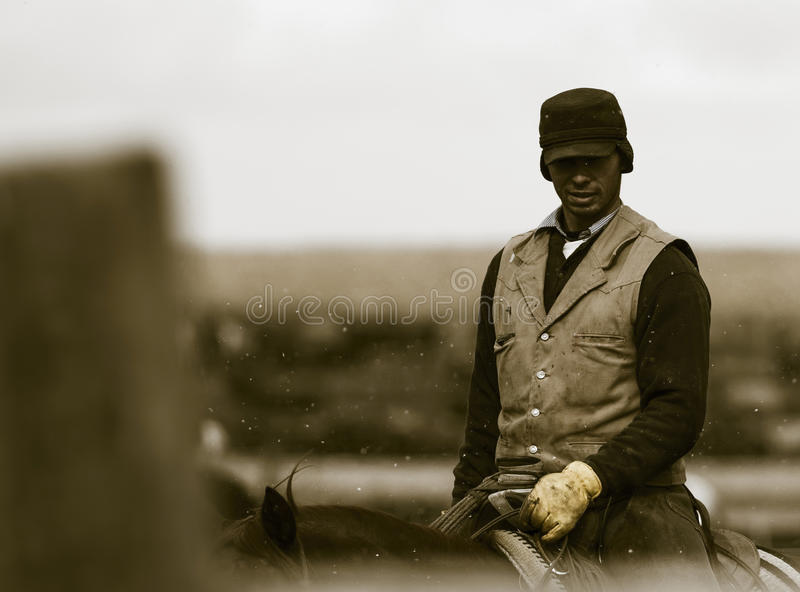 Working the Feedlot. An American Cowboy. Rides the Gates Checking on Feedlot Cattle in the Snow stock photo