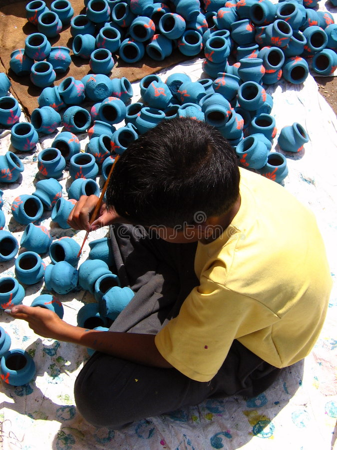 Working for festival. A kid paints pots to be sold during diwali festival. Child Labor is a criminal offence in India stock photo