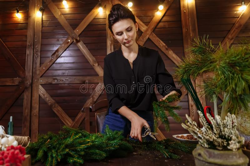 Working Florist Woman with Christmas Wreath. Young Cute smiling Woman designer preparing Christmas Evergreen Tree Wreath royalty free stock images