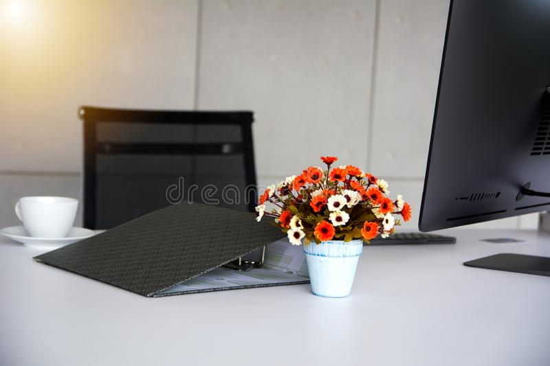 Working folder and accessories put on working table ready to morning assignment. Working folder and accessories decorated with bunch of flower put on working royalty free stock photo