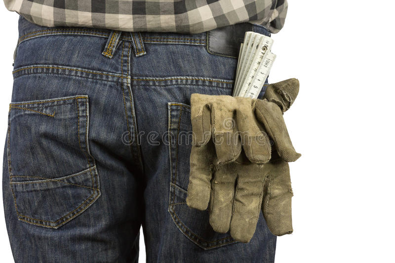 Working. Folding rule and working gloves in a trouser pocket royalty free stock photos