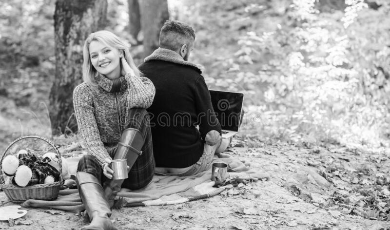 Working on fresh air. Happy loving couple relaxing in park with laptop. Always at work. Man freelance worker internet stock photography