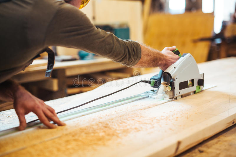 Working with fretsaw. Woodworker cutting board with fretsaw stock photo
