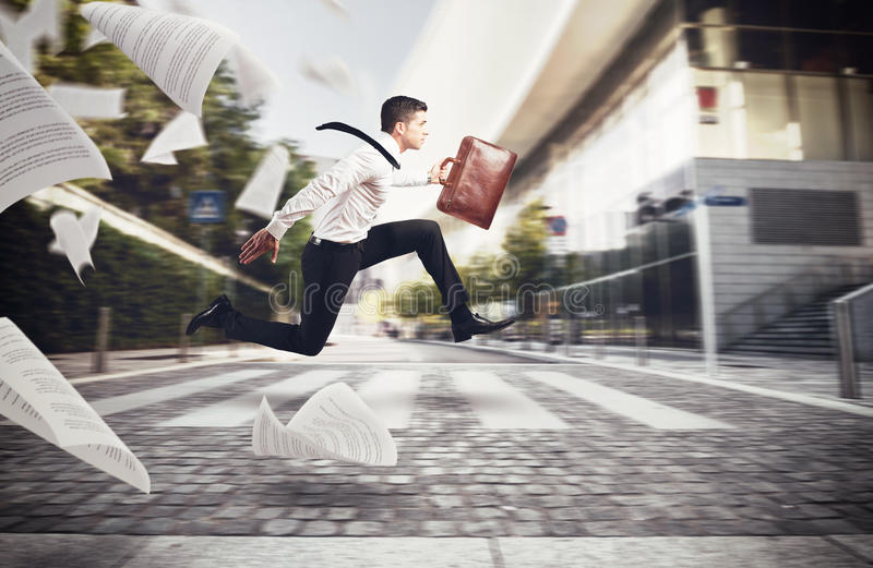 Working at full speed. Businessman runs on street to go to work with his bag stock image